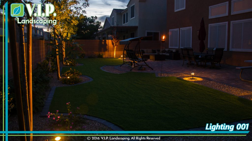 Backyard design that combines low voltage lights, turf, pavers, pebble rocks, plants and trees