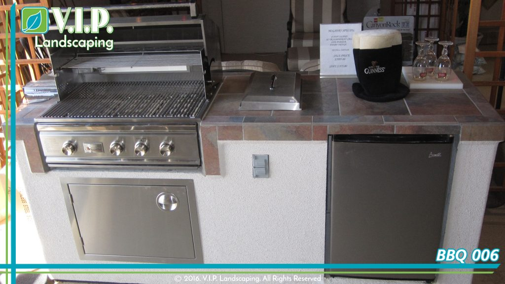 Outdoor kitchen with stainless steel barbeque, mini fridge. Tile countertop